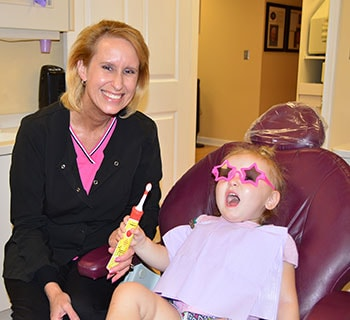 Dental hygienist teaching little girl the importance of brushing her teeth